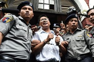 Myanmar journalist Wa Lone escorted by police after being sentenced by a court to jail in Yangon, on Sept 3, 2018.