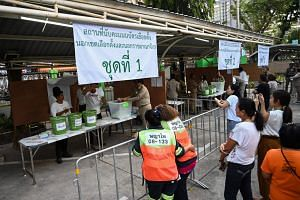 People watch as electoral officials count votes at a polling station in Bangkok on March 24, 2019, after polls closed in Thailand's general election.