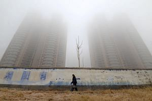 A woman wearing a mask walks past buildings on a polluted day in Hebei, China, on Jan 12, 2019.  More than a million premature deaths in China each year are attributed to foul air.