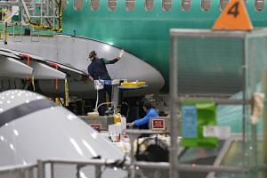 A Boeing employee works on the fuselage of a Boeing 737 in the company's factory in Renton, Washington, on March 27, 2019.