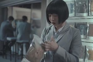 The ad then cuts to a grey, industrial city that resembles Tokyo, where an Asian woman buys a bag of dirty clothes previously worn by the men.