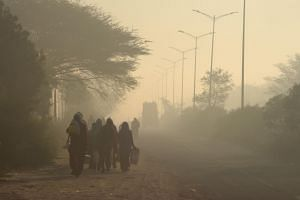 People walk amid heavy smog in Gurgaon, India, on March 7, 2019. The more immediate effects of air pollution, like itchy eyes and coughing, tend to be highlighted by people, rather than the risks from chronic exposure, pointing to the fact that peopl
