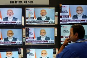 Indian Prime Minister Narendra Modi - shown here on TV screens inside a Mumbai showroom - addressing the nation yesterday to announce the successful anti-satellite missile test. He said that a missile travelled nearly 300km from earth and hit the sat