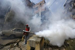 A Venezuelan health worker fumigates the Valle slum to help control the spread of the mosquito-borne Zika virus in Caracas, in 2016.