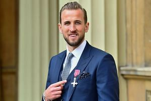 Kane poses wearing his medal after being appointed Member of the Order of the British Empire (MBE).