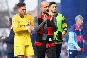 Guardiola (centre) and goalkeeper Ederson (left) react after beating Fulham.