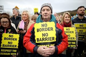 Protesters against any border between Ireland and Northern Ireland because of Brexit hold placards at the Carrickcarnan border between Newry in Norther Ireland and Dundalk in the Irish Republic.