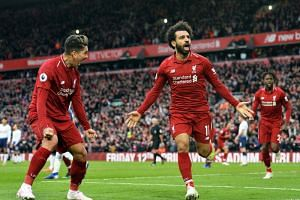 Liverpool players Roberto Firmino (left) and Mohamed Salah celebrate their 2-1 lead during the English Premier League soccer match between Liverpool FC and Tottenham Hotspur at Anfield in Liverpool, Britain, on March 31, 2019.