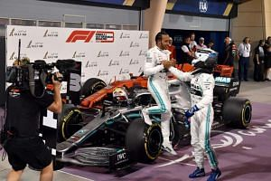 Mercedes' British driver Lewis Hamilton (left) celebrates with his teammate Mercedes' Finnish driver Valtteri Bottas after winning the Formula One Bahrain Grand Prix at the Sakhir circuit in the desert south of the Bahraini capital Manama, on March 3