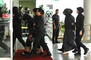 Indonesian national Siti Aisyah (second from left) and Vietnamese national Doan Thi Huong (second from right) being escorted by Malaysian police at the Shah Alam High Court, outside Kuala Lumpur on March 11, 2019.
