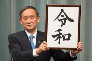 Japan's Chief Cabinet Secretary Yoshihide Suga holds up the new era name, Reiwa, during a press conference in Tokyo, on April 1, 2019.