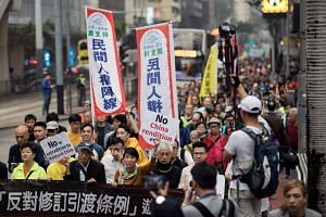 Thousands of people taking part in a march in Hong Kong yesterday to protest against a government plan to change extradition laws that would grant the city's leader executive power to send fugitives to jurisdictions not covered by existing arrangem
