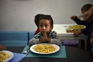 A child prays before eating at the Kapuy Foundation shelter in Venezuala, where shortage of food and medicines is hitting hard on the population.