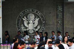 Visa applicants wait in line outside the US embassy in Beijing in June 2012.
