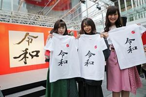 """Women taking their commemorative photos of the printed T-shirts with the new era name """"Reiwa"""" distributed for free at an event in Tokyo on April 1, 2019."""