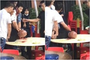 A video of the incident which was sent to citizen journalism site Stomp showed three men pinning down a 51-year-old man, who is bald, on a table in the coffee shop.