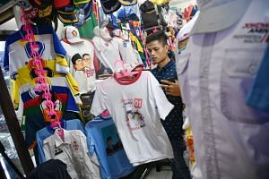 Mr Acep Abdul Aziz (above) said his shop at Jakarta's historic market, Pasar Senen, is seeing a 50 per cent increase in orders for election merchandise such as T-shirts, caps, jackets, banners and name cards. Buttons featuring images of presidential