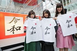 """Women showing off T-shirts printed with the new era name """"Reiwa"""". The T-shirts were distributed for free at an event in Tokyo on Monday."""