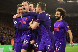 Liverpool's Jordan Henderson (second left) celebrates with team mates after scoring their third goal.