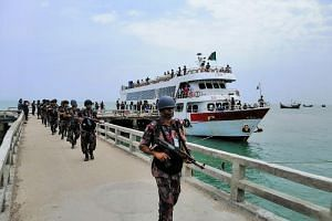 Border Guards Bangladesh paramilitary personnel carrying assault rifles disembark as they have been deployed on Saint Martin's island, a small island in the Bay of Bengal in Teknaf, on April 7, 2019.