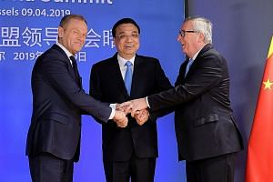 Summit chair Donald Tusk (left) and European Commission head Jean-Claude Juncker welcoming Chinese Premier Li Keqiang in Brussels. Mr Li's pledge at the annual EU-China leaders meeting yesterday follows similar offers to the United States and potenti