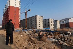 A man looks at a shantytown to be redeveloped, next to apartment buildings, in Fu county in the south of Yanan, Shaanxi province, China.