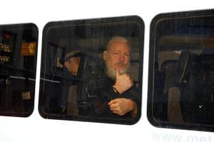 WikiLeaks founder Julian Assange in a police van after he was arrested by British police outside the Ecuadorian embassy in London, on April 11, 2019.