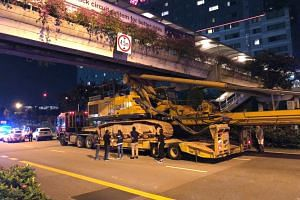 A crane collided with the underside of an overhead bridge along Jurong Town Hall Road on April 13.