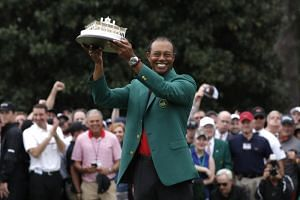 Tiger Woods of the US holds up the Masters trophy and wears the green jacket as he celebrates after winning the his win in the 2019 Masters.