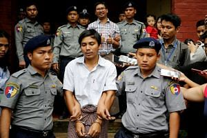 Detained Reuters journalists Kyaw Soe Oo and Wa Lone are escorted by police as they leave after a court hearing in Yangon in 2018.