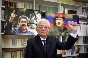 Venezuela Permanent representative to the United Nations in Geneva, Ambassador Jorge Valero poses between photographs of President Nicolas Maduro (left) and late President Hugo Chavez, at the permanent mission in Geneva on April 16, 2019.