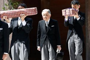 Japan's Emperor Akihito (centre), flanked by Imperial Household Agency officials carrying two of the so-called