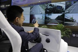 A visitor experiences a remote self-driving car during a media day of the Auto Shanghai 2019 motor show in Shanghai, on April 17, 2019.