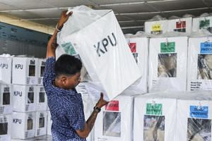 An election official carries a ballot box after the election in Medan, North Sumatra, Indonesia, on April 18, 2019.