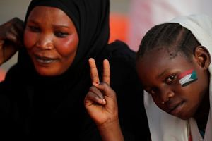 A girl with a painted Sudanese flag on her face makes victory sign as she is accompanied by her mother in front of the Defence Ministry.