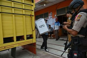 An Indonesian election worker unloads a ballot box as police provide security at a polling station ahead of the April 17 elections in Trumon, Southern Aceh.