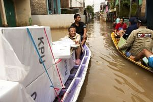 Indonesian election officials transporting ballot boxes from polling stations on a boat in a flooded part of Bandung in West Java on Thursday. The General Elections Commission has about a month to announce official results of the election, in which m