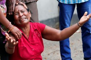 A relative of a victim of the explosion at St Anthony's Church reacts at the police mortuary in Colombo.