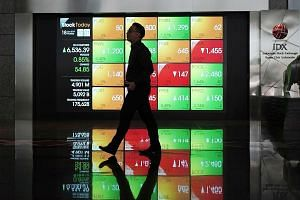 An electronic board displaying stock prices at the Indonesia Stock Exchange in Jakarta on Thursday. The Jakarta Stock Exchange ticked up past 6,500 points in trading after election day. The bourse has gained more than 5 per cent since January, while