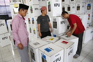 District employees count and check ballot boxes a day after the general elections at a village in Depok, Indonesia, on April 18, 2019.