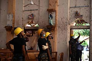 Security personnel inspect the interior of St Sebastian's Church in Negombo, on April 22, 2019.
