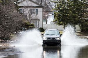 A car crosses a flooded street in Laval, Canada, on April 21, 2019, as the authorities remain on high alert in expectation of more surges of water across southern Quebec.