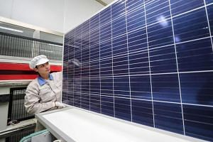 A worker checks newly made solar panels at a factory in Lianyungang in Jiangsu, China.