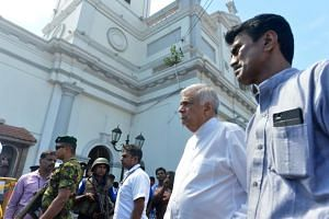 Sri Lankan Prime Minister Ranil Wickremasinghe (second from right) arrives to visit the site of a bomb attack at St. Anthony's Shrine in Colombo on April 21, 2019.