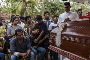 Mourners in Negombo, Sri Lanka, at the burial of three members of the same family who were killed in the suicide bomb attack at St Sebastian Church, on April 22, 2019.