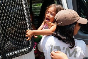 Members of the National Institute of Migration of Mexico (INAMI) detain a girl during an operation in the municipality of Pijijiapan, in the state of Chiapas, Mexico.