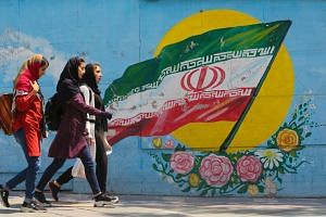Pedestrians walking in front of a mural showing the Iranian national flag in capital Teheran, on April 23, 2019.