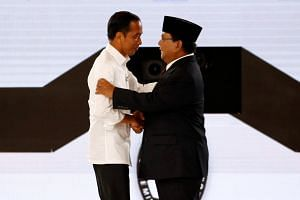 Indonesia's presidential candidate Joko Widodo shakes hands with his opponent Prabowo Subianto after a televised debate in Jakarta, on March 30, 2019.