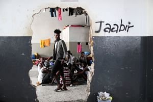 Migrants are seen at a detention centre in Tripoli.