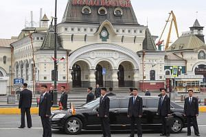 Above: North Korean leader Kim Jong Un attending a welcome ceremony after arriving at Vladivostok railway station in his private train yesterday. Right: Bodyguards around a limousine that was part of Mr Kim's motorcade outside Vladivostok railway sta